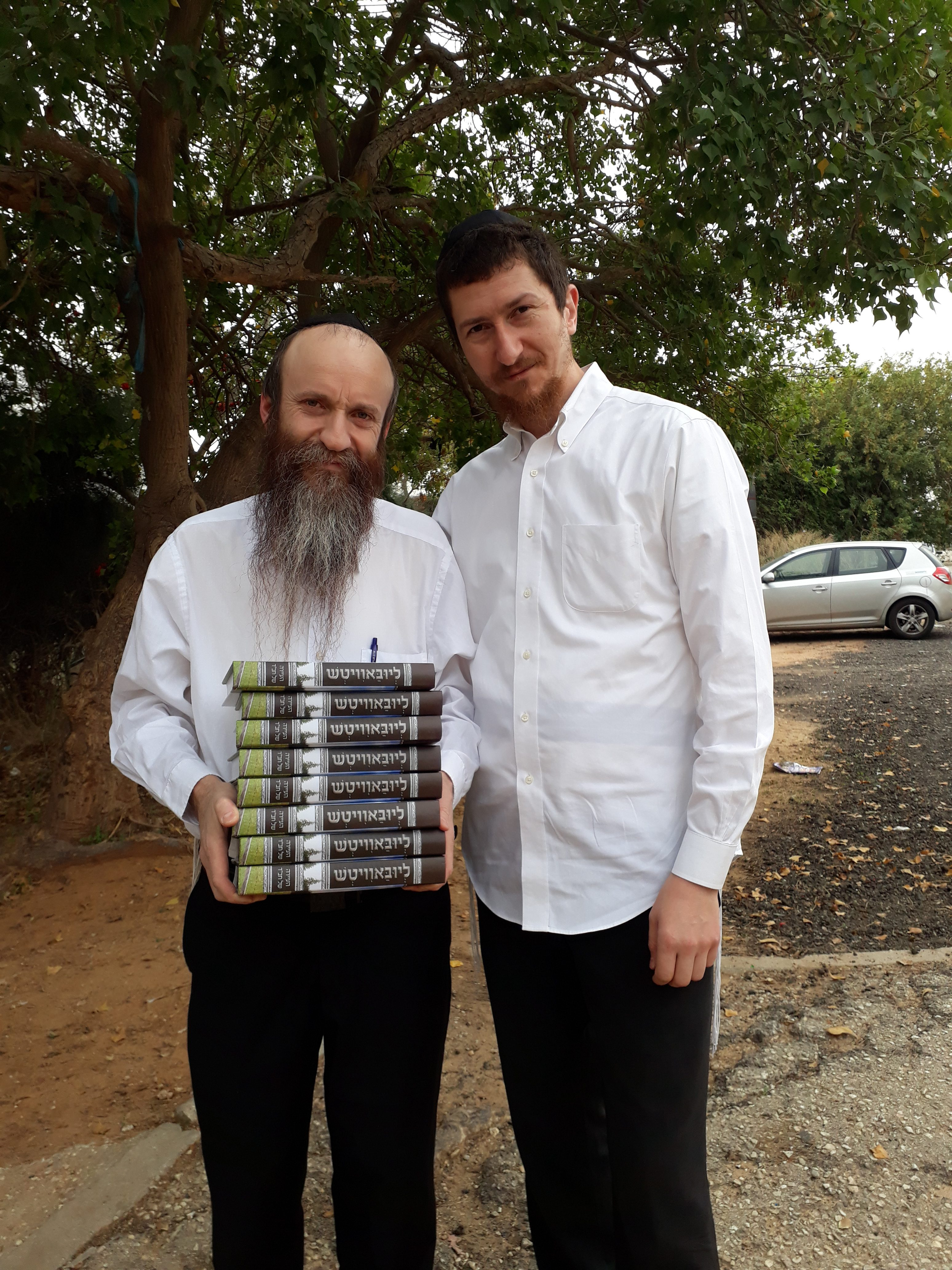 הרב אלישיב, עורך הספר, נושא ערימת ספרים בידו