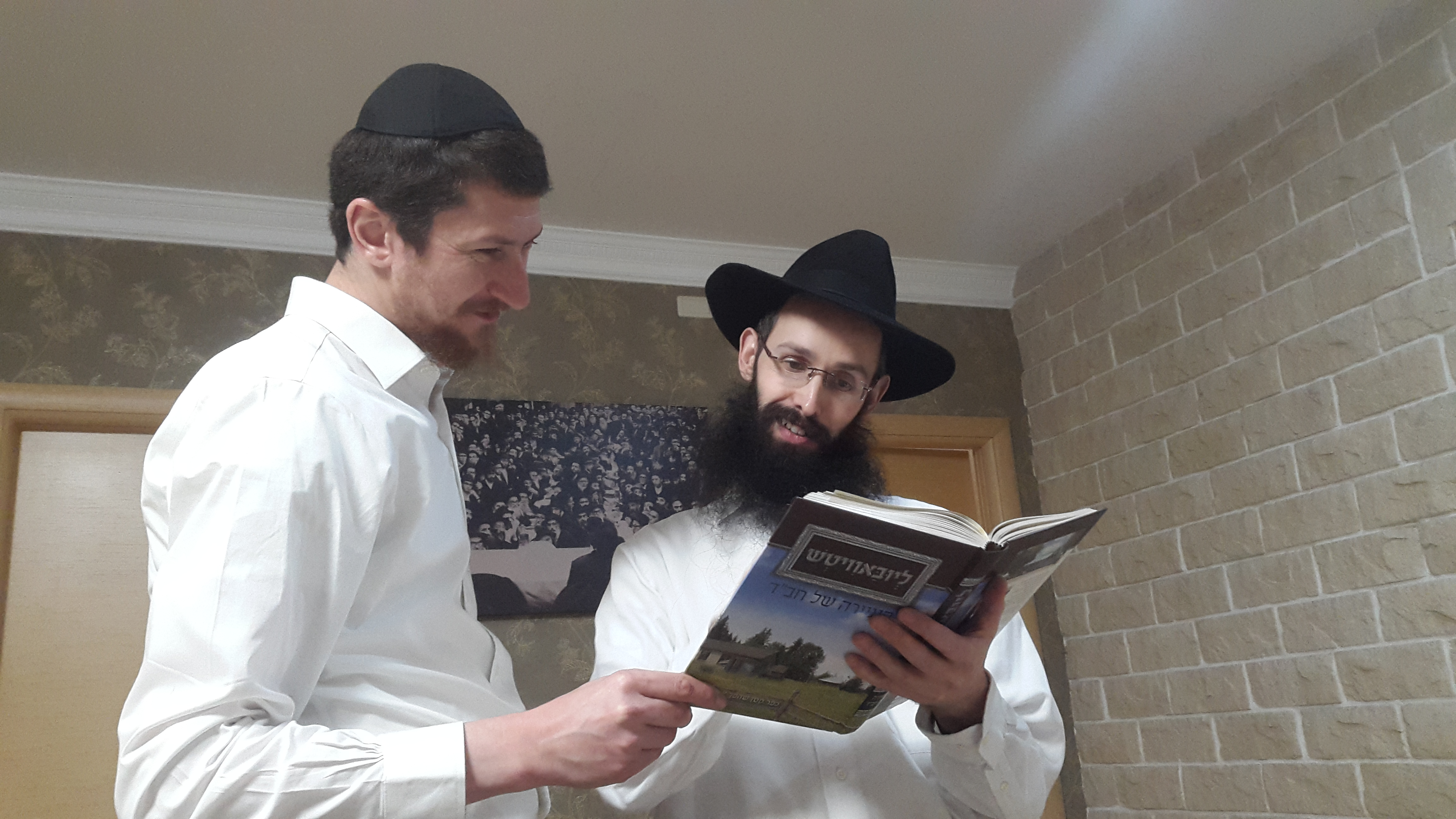 הרב לוי מונדשטיין, שליח הרבי לסלומלנסק הסמוכה לליובאוויטש מקבל את הספר ומעיין בו