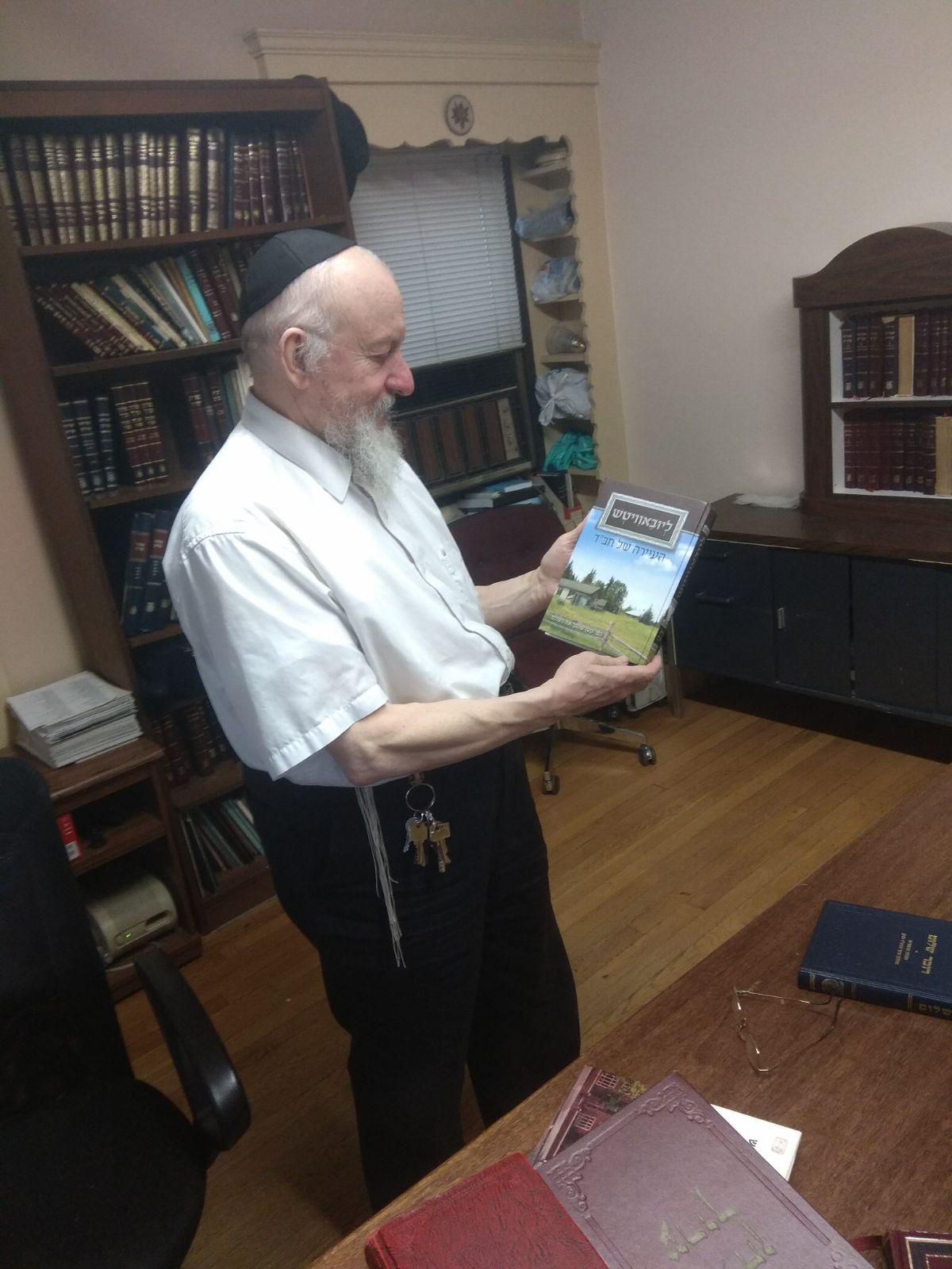 הרב בערל לוין, מנהל הספריה של הרבי, מביט בספר