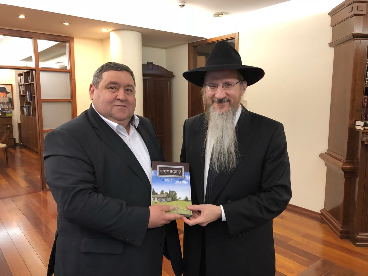 הרב בערל לאזאר מעניק את הספר לתומך של העיירה ליובאוויטש