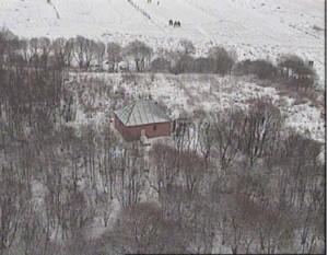 """האהל (משופץ), ולידו נראה הציון של הרבנית רבקה ע""""ה (תצלום אויר - חורף תשנ""""ב 1992). לשמאל האהל - בית החיים (בין העצים). לימין האהל - הדרך מהעיירה לאהל. בדרך נראים כמה שמתקרבים לאהל; אחדים - ליד העצים ואחדים עדיין בשדה (על השלג)."""